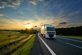 White truck driving on the asphalt road in rural landscape at sunset