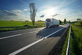 White trucks driving on asphalt road along the green fields in rural landscape at sunset