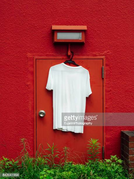 White T-shirt hangs on the red wall