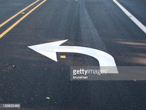 White turn left arrow painted on asphalt