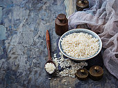 White uncooked rice on concrete background. Selective focus
