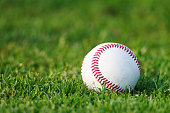 Baseball on the clear green grass turf close-up as macro shot with copy space on the left and top