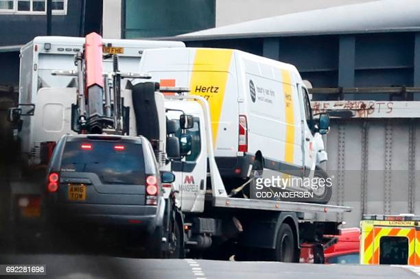 A white van used in the attack on London Bridge is seen hoist on top of a flatbed truck as police work on London Bridge in London on June 4 as part...
