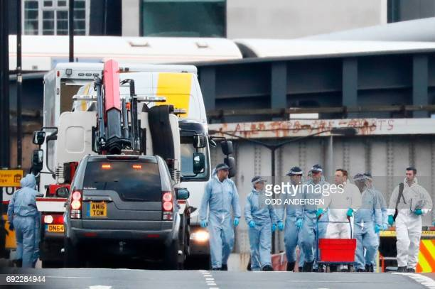A white van used in the attack on London Bridge is seen hoist on top of a flatbed truck as police forensics officers work on London Bridge in London...