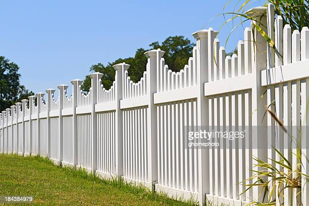 White vinyl yard fence with green grass