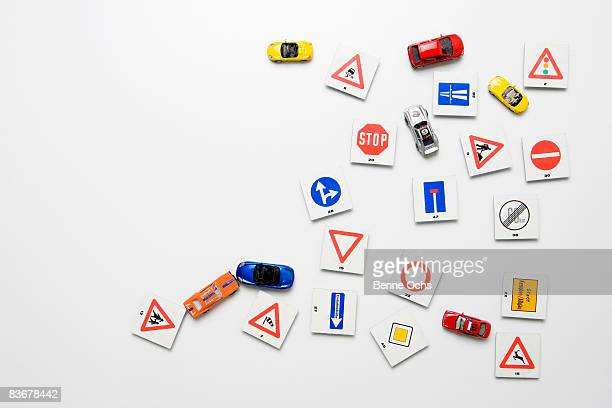 A white wall with miniature road signs & toy cars