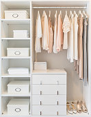 white wardrobe on wooden floor with dress hanging on rail