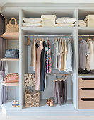 white wardrobe with shirts and pants hanging on rail