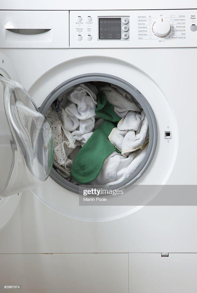 white washing in machine one green sock : Stock Photo