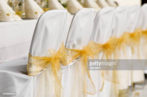 White wedding chairs with golden ribbon