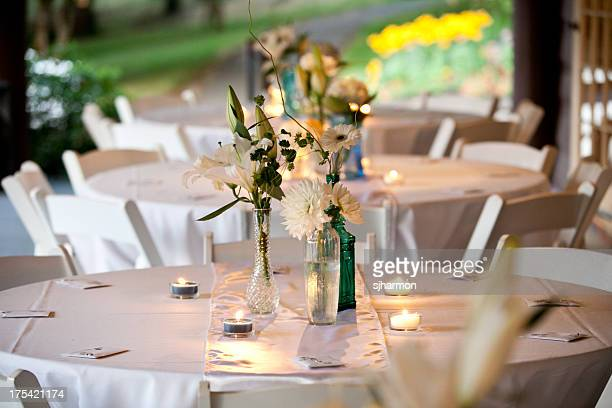 White Wedding Tables With Flowers Candels and Carafes Blurred Background