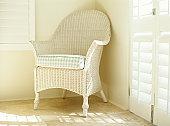 White wicker chair in corner of room
