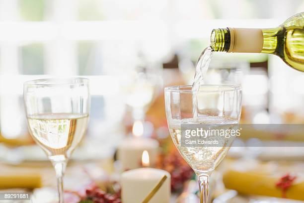 Weißwein, gegossen in Glas auf einem Tisch