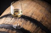 Glass of white wine standing on an oak barrel in a cellar