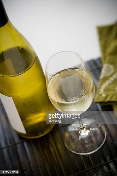Vin blanc sur la table avec bouteille à proximité