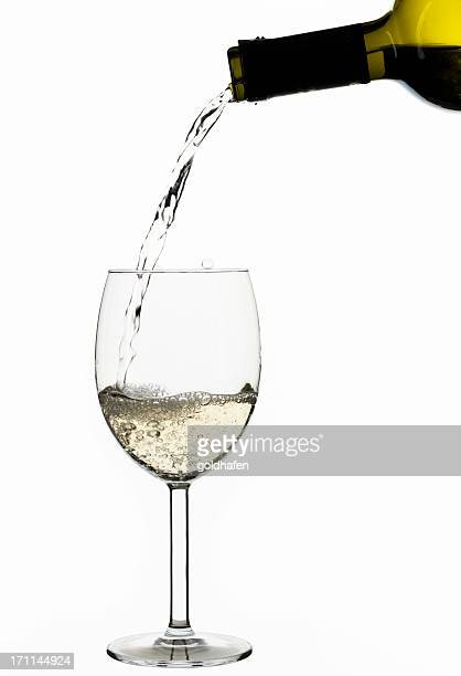white wine poured out of a green bottle - isolated