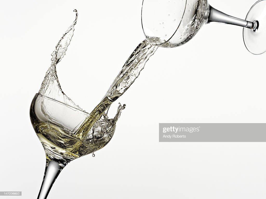 White wine pouring from one glass into another : Stock Photo