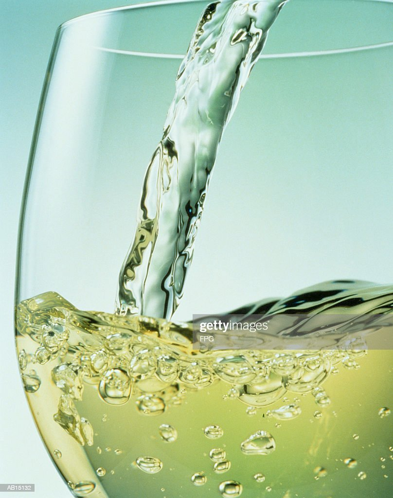 White wine pouring into glass, close-up : Stock Photo