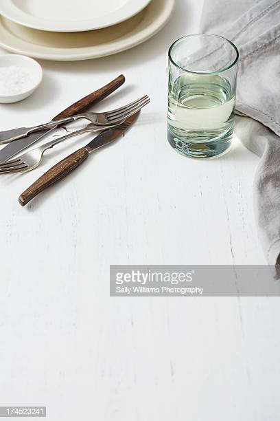 A white wood tabletop with dinner place setting