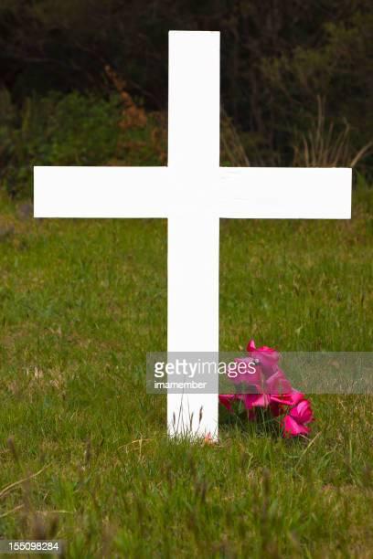 白の木製のクロスにレッドの花の緑の芝生
