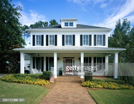 White wooden house, flowers blooming around front porch