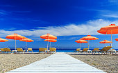 White wooden walkway leading to the beach with umbrellas and sunbeds
