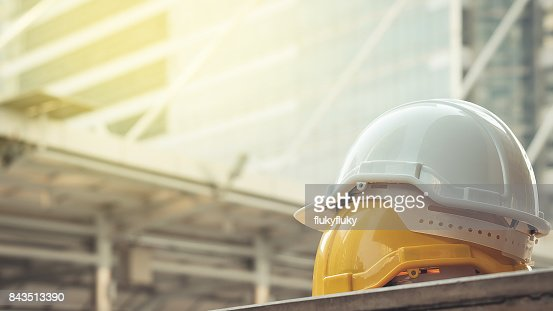 white, yellow hard safety helmet hat for safety project of workman as engineer or worker, on concrete floor on city : Stock Photo