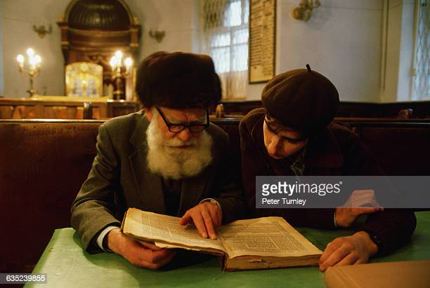 A whitebearded elderly man reads with a younger man in a synagogue in Moscow