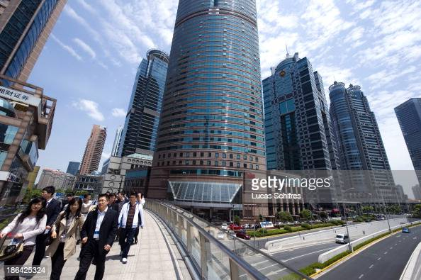 Whitecollar workers walk to their lunch break in Pudong Luziajui business district in Shanghai China on May 24 2011