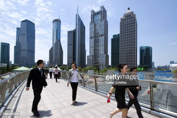 Whitecollars walk to their lunch break in Pudong business district in Shanghai China on May 24 2011