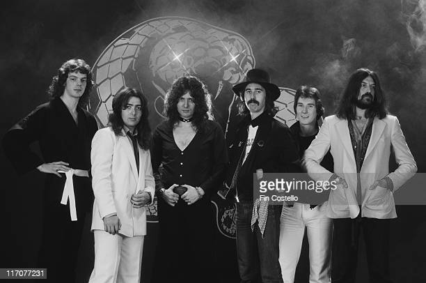 Whitesnake British rock band pose standing in front of the band's snake logo for a group studio portrait in Camden London England Great Britain in...