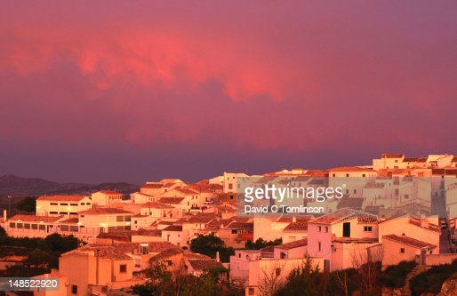 Whitewashed village houses beneath pink sky.