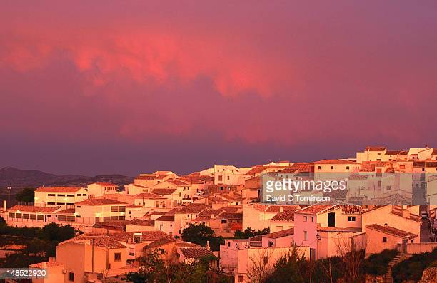 Whitewashed village houses beneath pink sky.