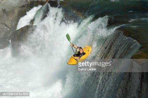 Whitewater kayaker descending waterfall