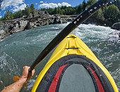 Whitewater kayaker paddling rapids in river