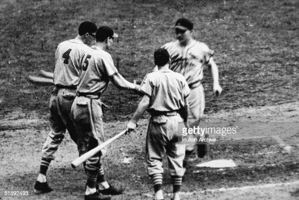 Whitey Kurowski of the St Louis Cardinals runs across home plate after hitting a home run as his teammates Marty Marion and Walker Cooper...