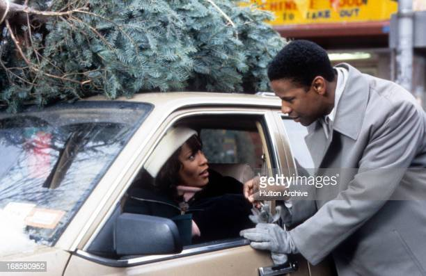 Whitney Houston is approached by Denzel Washington in a scene from the film 'The Preacher's Wife' 1996