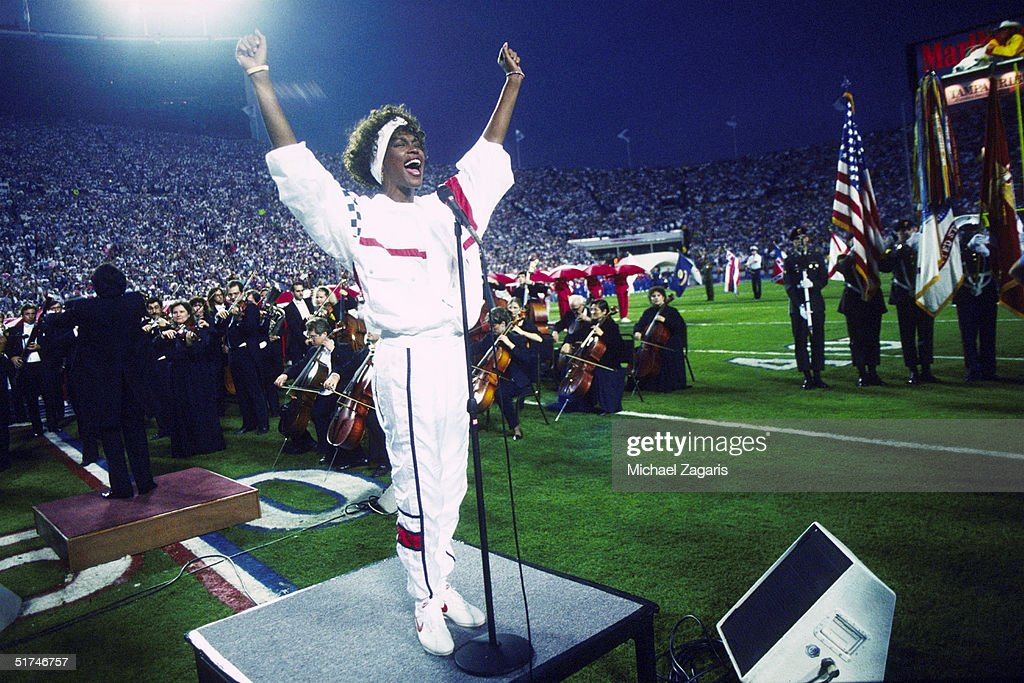 Whitney Houston sings the National Anthem during the pregame show at Super Bowl XXV while tens of thousands of football fans wave tiny American flags in an incredible outburst of patriotism during the Persian Gulf War on .