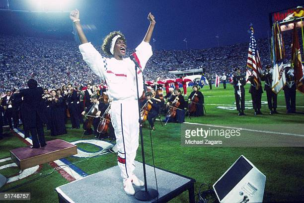 Whitney Houston sings the National Anthem during the pregame show at Super Bowl XXV while tens of thousands of football fans wave tiny American flags...