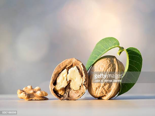 Whole and broken walnuts on a wooden table illuminated by sunlight