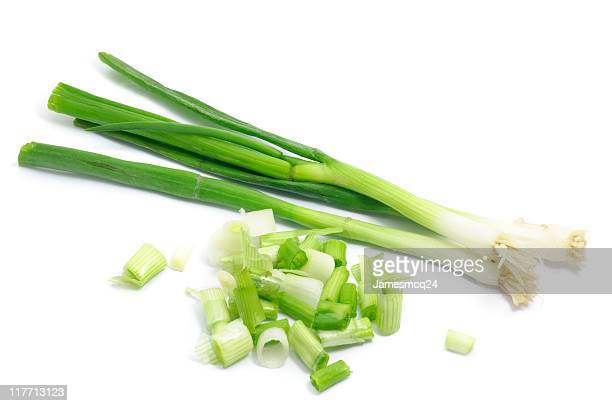 Whole and chopped green onions isolated on white background