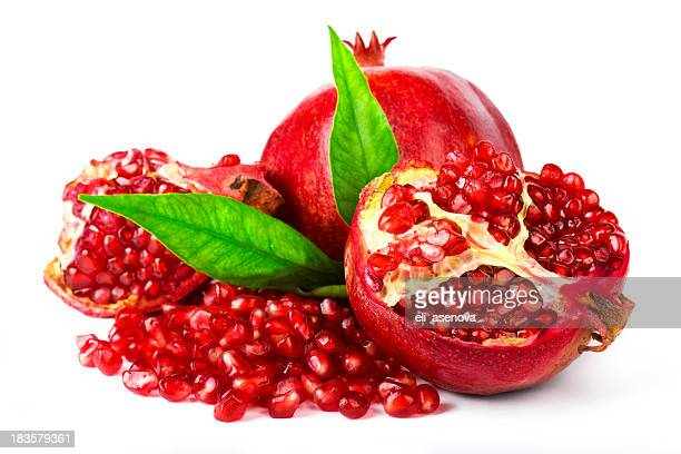 Whole and cracked pomegranate with leaves and seeds