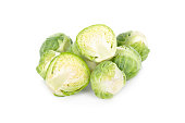 whole and half cut uncooked Brussel sprouts on white background