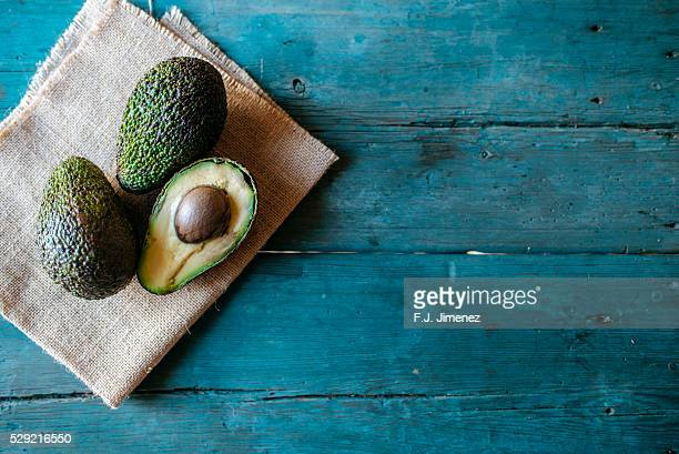 Whole and halved avocado on wooden table