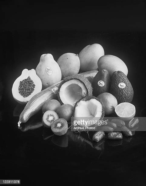 Whole and halved fruits on black background, close-up