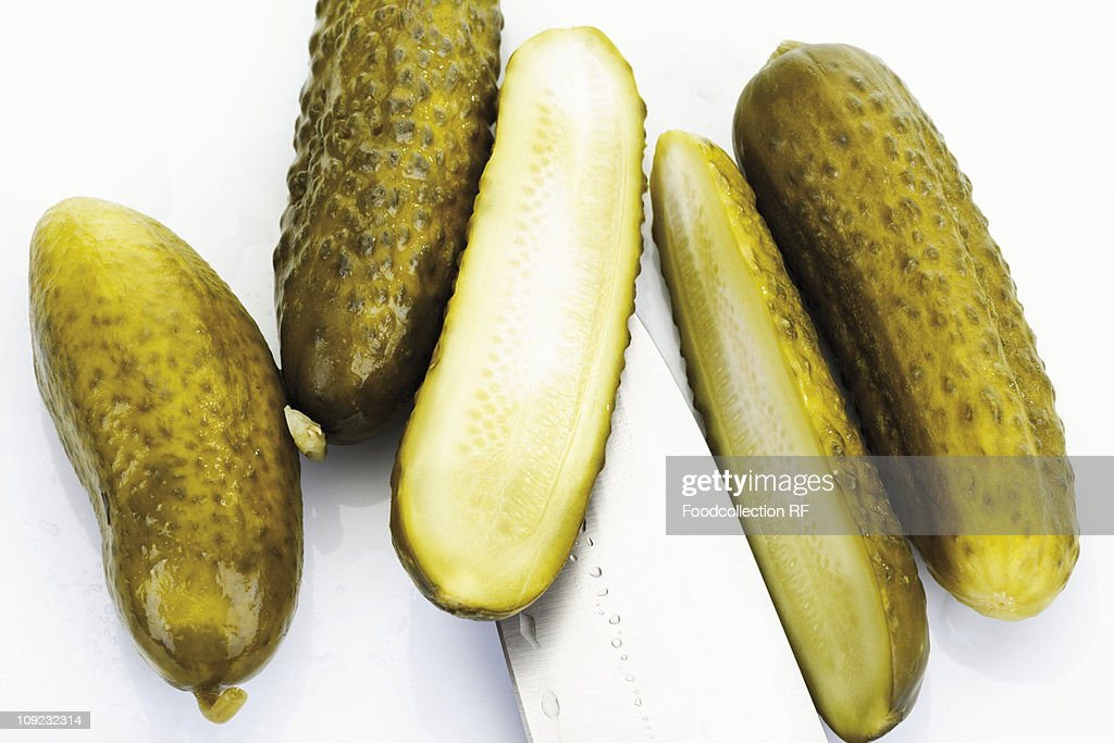 Whole and halved pickled gherkins on white background : Stock Photo