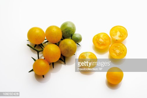 Whole and halved yellow tomatoes on white background