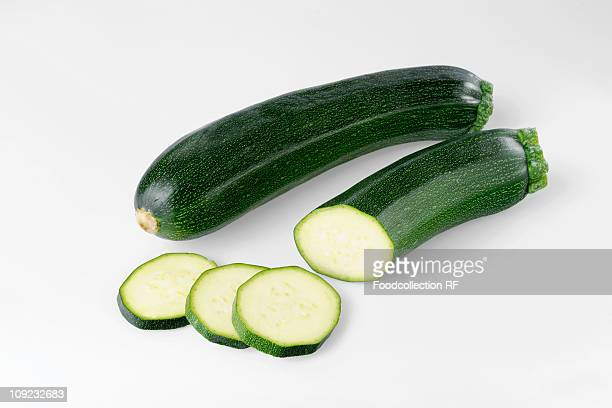 Whole and sliced courgettes on white background
