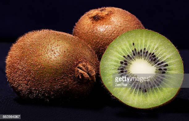 Whole and sliced kiwi fruit on black background