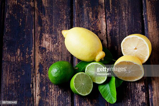 Whole and sliced lemons and limes on dark wood